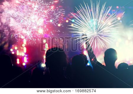 Fireworks and crowd celebrating the New Year wit fireworks- holiday celebration background