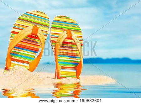 Beach sandals on the sandy coast. Summer holiday and vacation concept.
