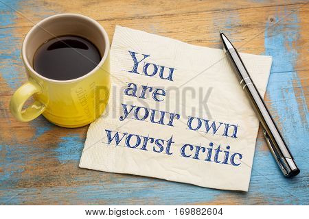 You are your own worst critic - handwriting on a napkin with a cup of espresso coffee
