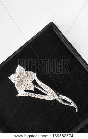 Elegant diamond floral brooch in black jewel box closeup
