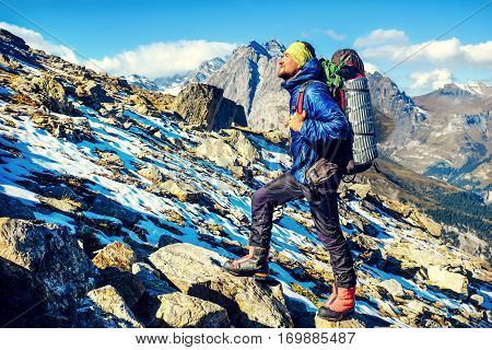 Hiker with backpacks reaches the summit of mountain peak. Success freedom and happiness achievement in mountains. Active sport concept.