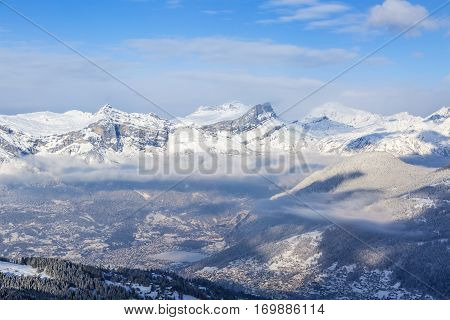 Chain of peaks in Alps above the clouds and villages