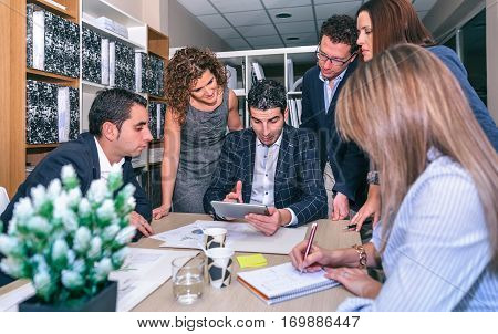 Teamwork looking document in electronic tablet around of business chief in company headquarters