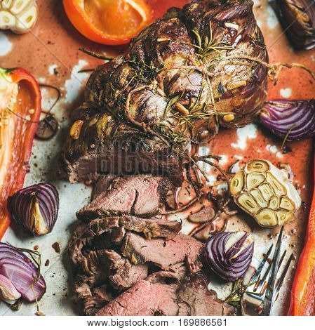 Cooked Roastbeef meat with roasted vegetables and herbs in metal baking tray, top view, selective focus. Slow food concept