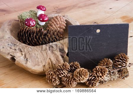 chalkboard and wooden bowl with pinecones and mushrooms on wooden table