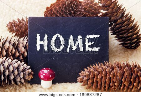 pinecones and chalkboard with the word Home written on it