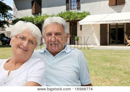 Pareja Senior sentado delante de una casa