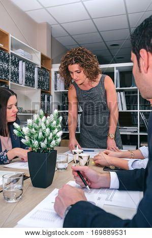 Businesswoman looking graphs in a business meeting to teamwork sitting at table in company headquarters