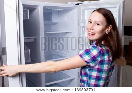 Attractive female teenager looking in empty refrigerator with shocked expression smile