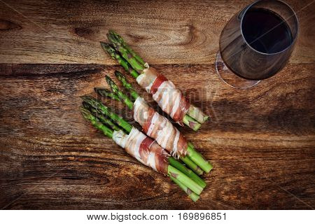 Green asparagus with bacon and a glass of red wine on a dark rustic wooden table