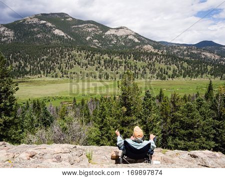 Rocky Mountain National Park, USA - July 15, 2015: Man in folding chair enjoying the scenery in Rocky Mountain National Park