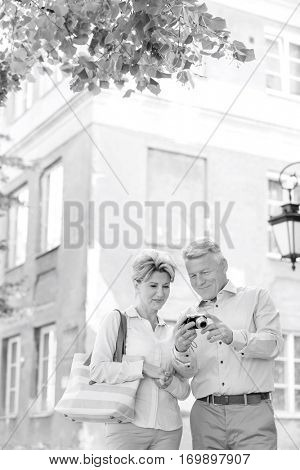Middle-aged couple reviewing photos on digital camera outside building
