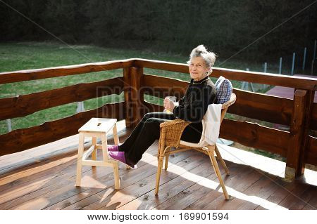Beautiful senior woman at home, sitting on rattan chair on wooden terrace, resting with feet up on wooden step stool.