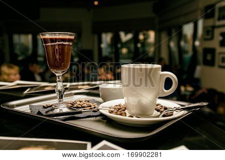 Flatware with coffee glasses and coffee beans in evening cafe. Toned image.