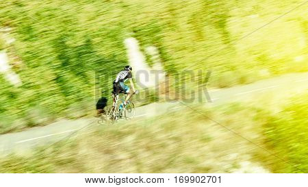 Healthy lifestyle - Fast motion biker climbing hill - defocused following of modern workout sportive on a warm sunny day in clean environment green forest