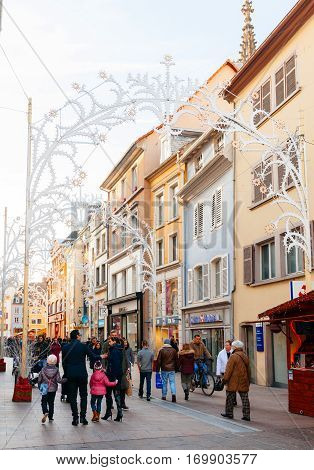 MULHOUSE FRANCE - DEC 12 2015: Shopping street Rue Merciere with Place Reunion in the bacground in central Mulhouse during Christmas Market with people entering shops to buy gifts and food