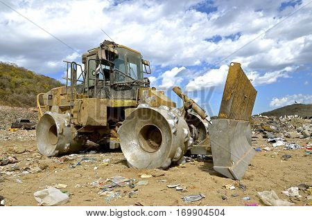 A huge tractor with a front end loader and metal wheels is used to move trash in a city dump