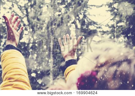 Girl's hands praying for the first snow and winter time.