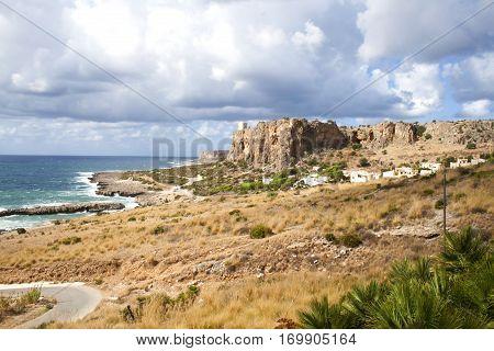 Medieval tower in top of a mountain facing the ocean (Cala Macari) near San Vito lo Capo, Sicily, Italy