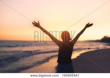 Silhouette Asian woman raise up hand freedom and enjoy view of beautiful sunset sky on tropical beach in twilight time at Phuket province Southern of Thailand