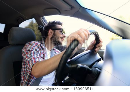 Portrait of successful young man driving car