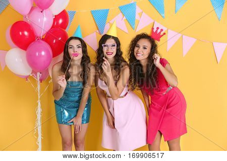 Beautiful young women at birthday party on yellow background
