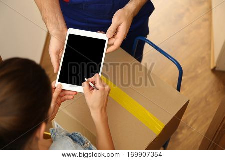 Young woman appending signature after receiving parcel from courier at home, closeup