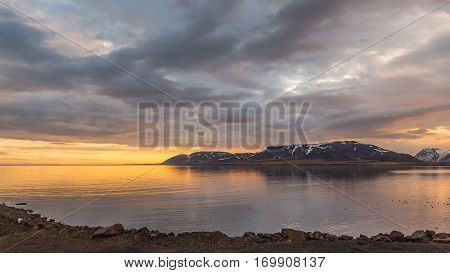 Cloudy sunset over the sea and headland northeast from Grundarfjordur Snaefellsnes peninsula Iceland.