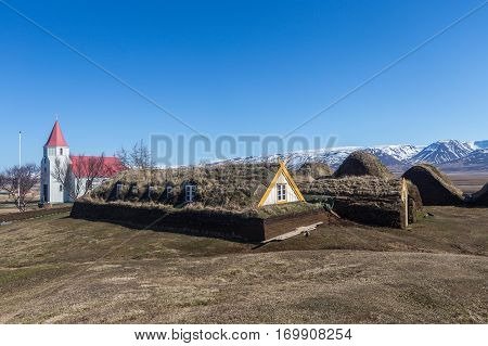 Historic turf-roofed farmhouses built with peat. The sod houses are flanked by a church while the background shows the mountain range around Olafsfjordur. Glaumbaer Varmahlid Iceland.