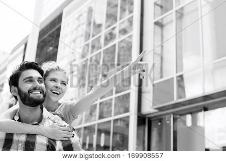 Cheerful woman showing something to man while enjoying piggyback ride in city