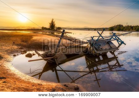 Old abandoned fishing boat wrecked stand on a beach with sunset.