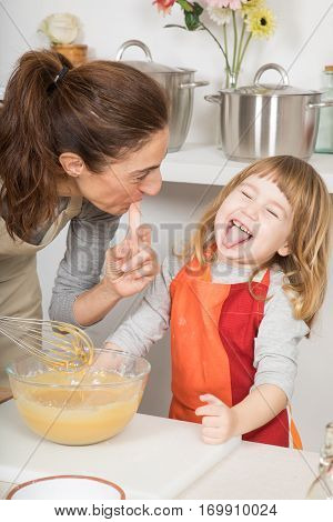 Laughing Child With Mother Cooking A Cake