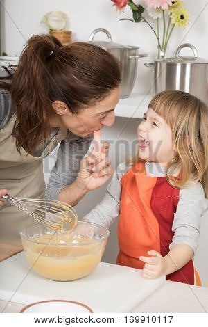 Laughing Mother And Child Tasting Whipped Cream With Finger