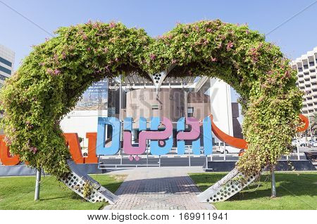 DUBAI UAE - DEC 6 2016: Heart gate made of flowers in front of Dubai Municipality building in Deira. Dubai United Arab Emirates Middle East