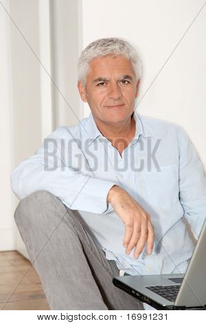 Senior man with laptop sitting on the floor