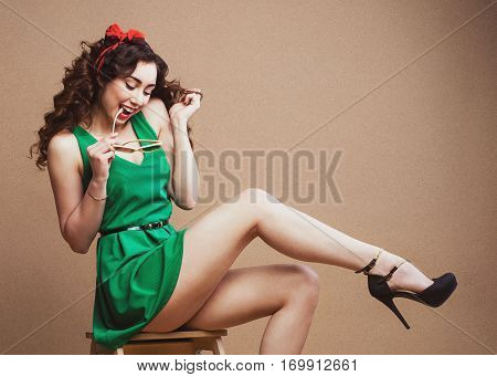 Curly Pin-up girl in green dress sitting on chair, having fun and her perfect legs at rough paper background. Stylish stusio shot. Flirt concept.