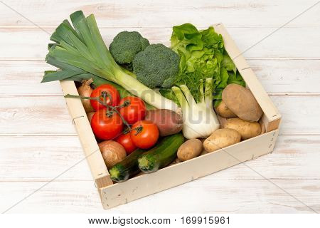 Wooden crate filled with a variety of fresh vegetables