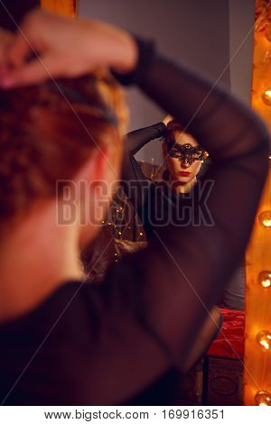 Old-fashioned woman face in mask looking into the mirror