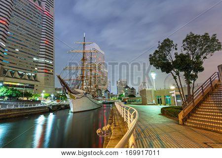 Cityscape of Yokohama with sailing ship at night, Japan