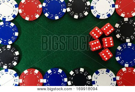 Framing of poker chips on green gaming table. Red dice inside frame of game chips  close up. Online game background. Casino chips on green textured backdrop.