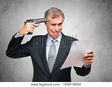 Desperate businessman pointing a gun to his head while reading a document