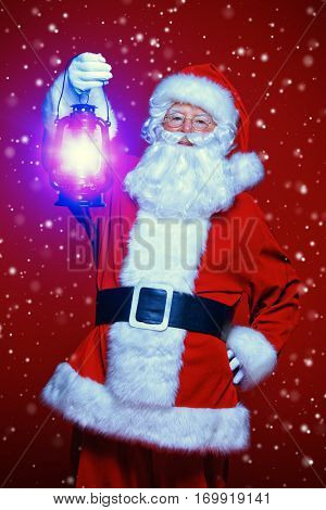 Christmas concept. Portrait of a fairytale Santa Claus holding lantern over red background. Magic time.