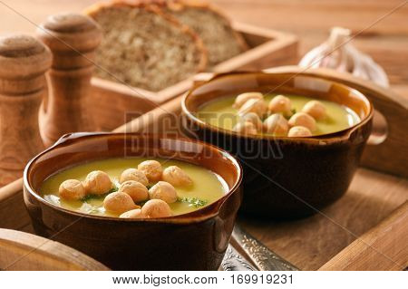 Vegetable cream soup with croutons on wooden tray.