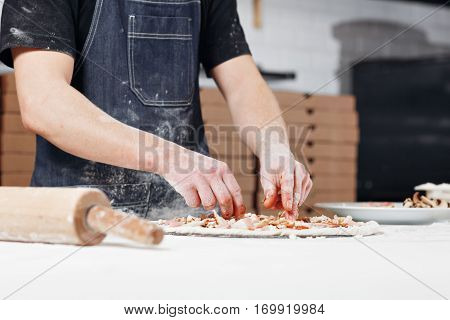 Cooking pizza. arranges meat ingredients on the dough preform. Closeup hand of chef baker in uniform blue apron cook at kitchen.