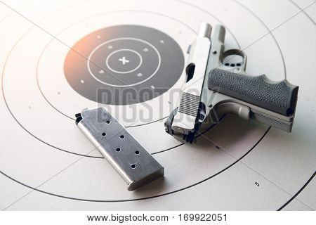 silver .45 pistol with magazine in safety position on bullseye target paper with flare