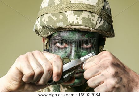 Close up view of soldier pulling safety pin out of fragmentation grenade, on grey background