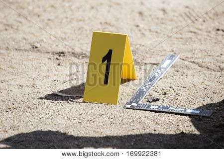 evidence marker and ruler scale of evidence with law enforcement hand background