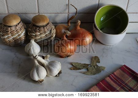 Kitchen corner with white garlic cloves, golden onions, pots and tea towel. White kitchen table with garlic, onions,straw pots, ceramic bowls and bay leaves.