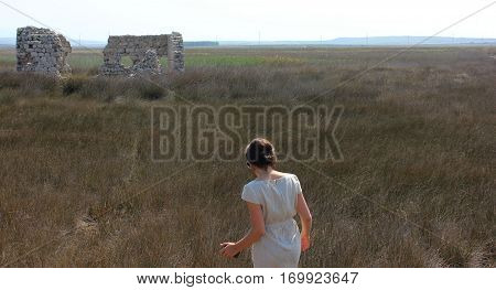 Young lady walking in field towards abandoned building remnants. wild southern field with lady moving to stoned building remnants.
