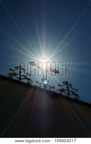 The sun's rays passing through the cross atop the church.